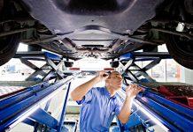 Ein Prüfer des TÜVs kontrolliert den Unterboden eines Autos.