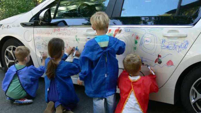 Kinder bemalen den Opel Ampera