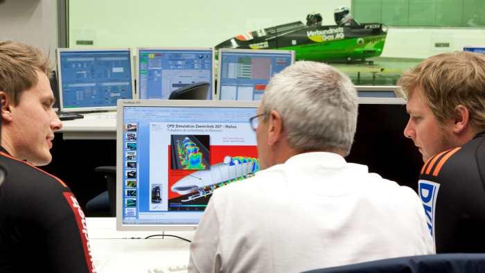 Bobsportler bei der Auswertung der Ergebnisse im Windkanal.