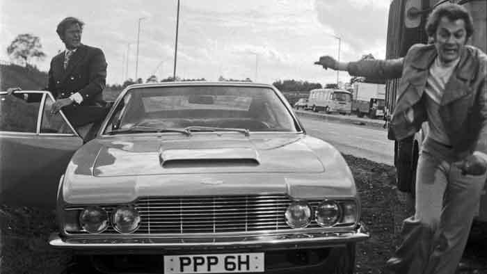 Roger Moore und Tony Curtis mit dem Aston Martin DBS.