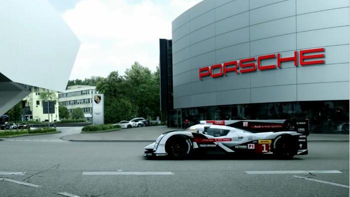 Ein Audi R18 fährt in dem Video bei Porsche vor.