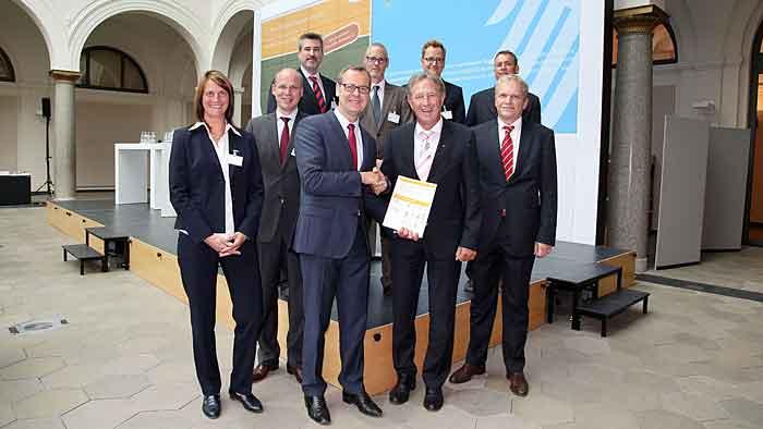Staatssekretär Norbert Barthle (Mitte) erhält den Forschungsbericht.